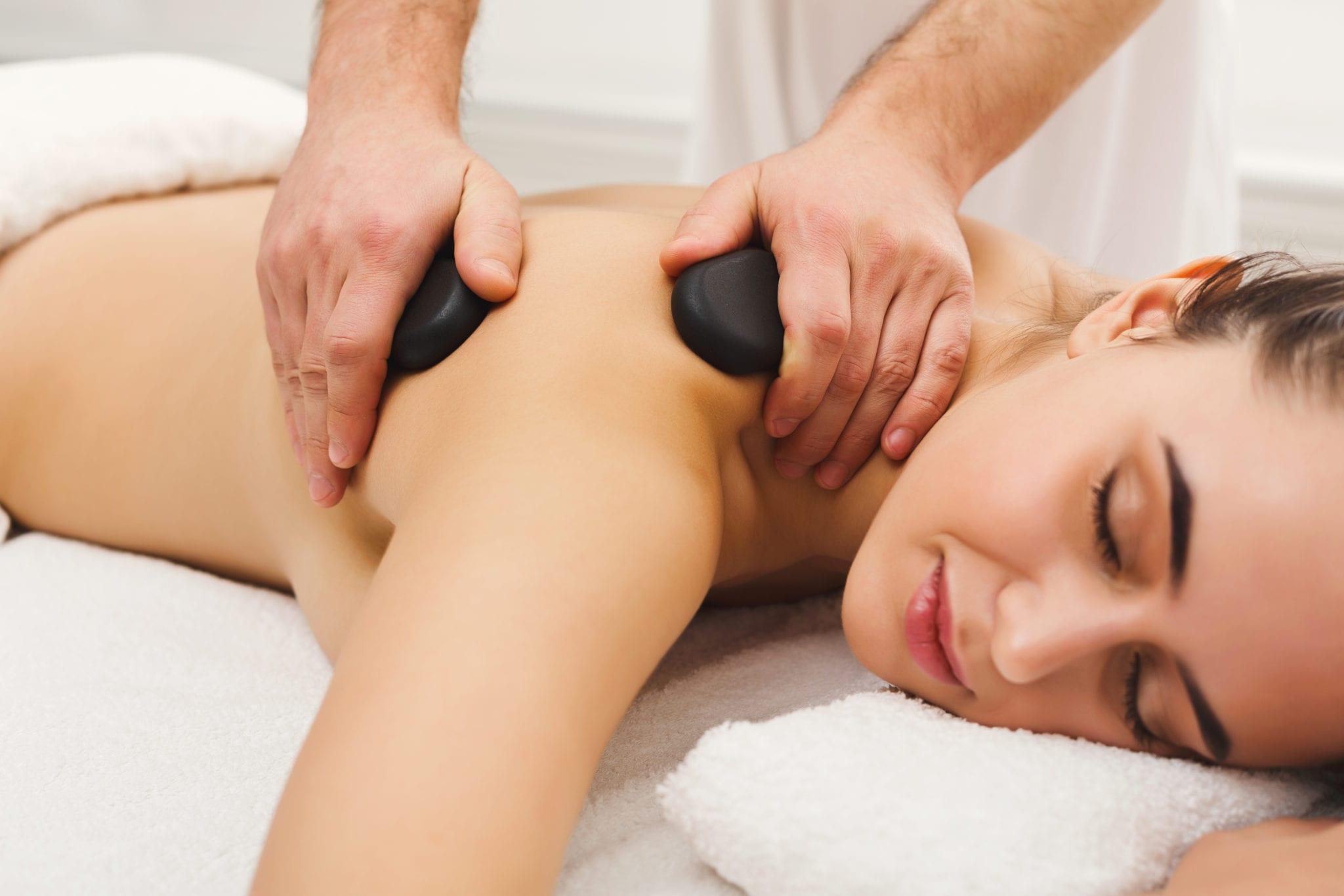 Woman getting hot stones massage at spa salon
